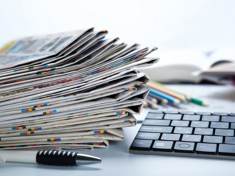 stack of newspapers and keyboard close-up on white