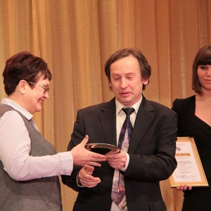 Владимир Пантелеев бережно вручает приз за Лучшую районную газету редактору Канских ведомостей Любови Цевун